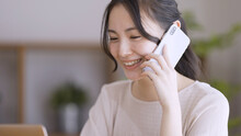 電話をしながらラップトップを使う若い女性