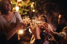 Group Of People Cheering And Celebrating With Champagne Glasses At Party Together