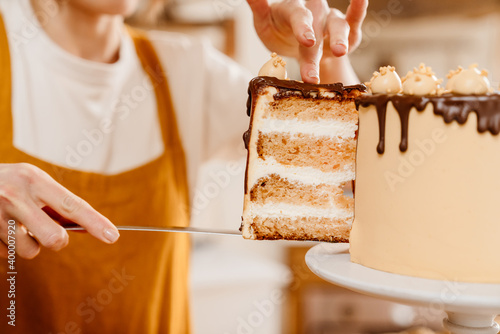 Fotografia Caucasian pastry chef woman showing piece of cake with chocolate cream