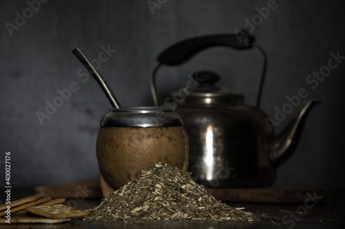 Foto Shot of a brown calabash, a kettle and a bag filled with tea herb called mate