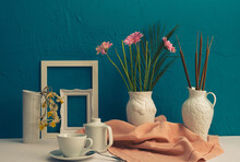 Gerbera, Dry Daffodils, White Photo Frame, A Cup With Coffee And A Teapot And Two Vases With Flowers On A Blue Background
