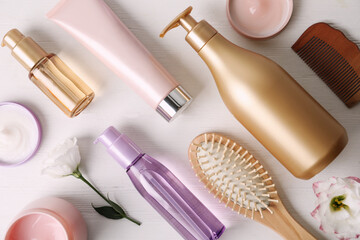 Flat lay composition with different hair products and accessories on white wooden table