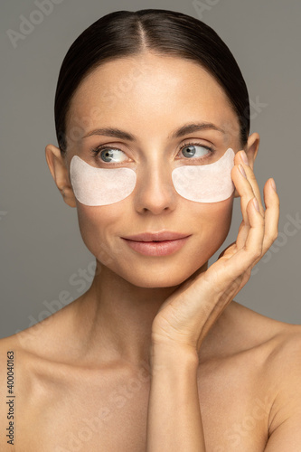 Fototapeta Woman applying hydrogel under-eye recovery patches enriched with collagen, vitamin E, provides intensive hydration and diminishes the signs of aging, helps reduse eye puffiness