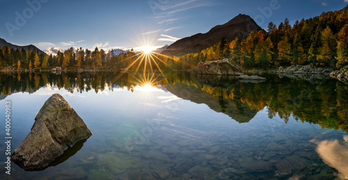 Obraz Panoramic shot of mountains and forests reflected in the lake - fototapety do salonu