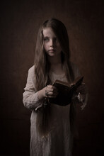 Young Girl In White Dress Holding Old Antique Bible And Rosary In Dark Studio Setting