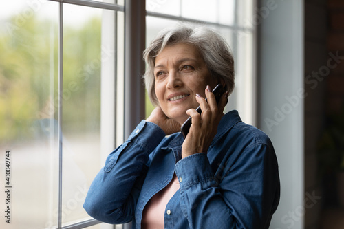 Obraz Happy middle aged 50s woman standing near window, enjoying pleasant mobile phone conversation with friends. Smiling dreamy older mature lady communicating distantly by smartphone call indoors. - fototapety do salonu