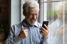 Overjoyed Emotional Middle Aged Mature Hoary Retired Man In Eyewear Looking At Smartphone Screen, Getting Message With Amazing News Or Celebrating Winning Online Lottery, Good Luck Success Concept.