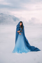 Art Photo. Fantasy Young Woman Fairy Elf In Blue Cape With Hood Stands In Cold Wind. Winter Nature Background, Mountains In The Clouds, Dramatic Sky White Snow. Girl Queen Walks In Dress, Silk Cloak