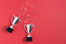 Winner Or Champion Silver Trophy Cups With Confetti On Red Background Top View.