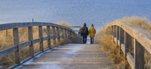 Mother And Son Walking On A Boardwalk To The Beach In Winter.