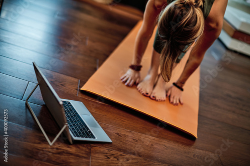 Woman practicing yoga at home with video tutorial. Wallpaper Mural