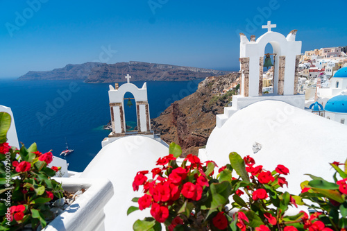 Fényképezés Red flowers bougainvillaea with background in Greek white ortodox church with be
