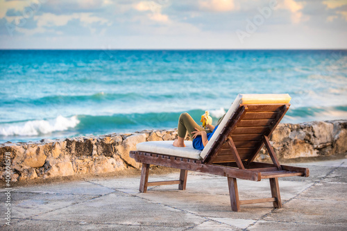 Papel de parede Person from the back laying on lounge beach chair looking at the ocean