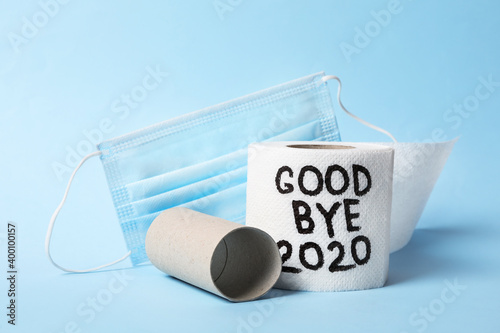 Photo Toilet paper roll with text Goodbye 2020 and medical face mask on light blue bac