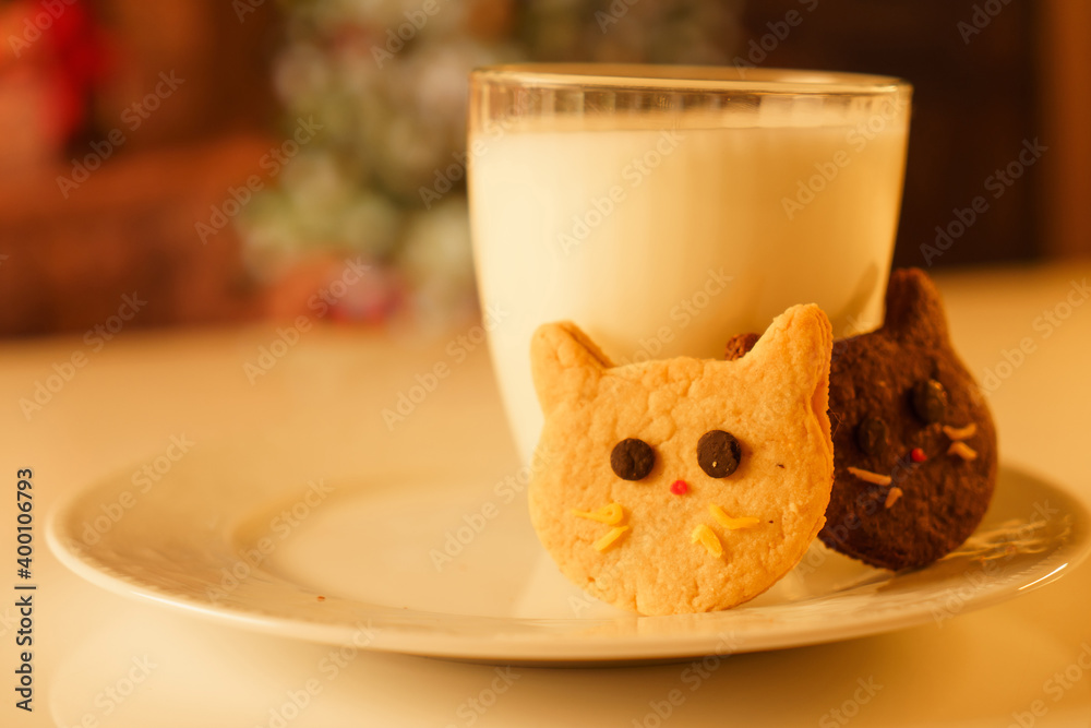 Fototapeta Cocoa and gingerbread cookies for New Year's Eve and Christmas themed. An image of a cat-like cookie and a glass of milk with a Christmas tree and fireplace in the background.
