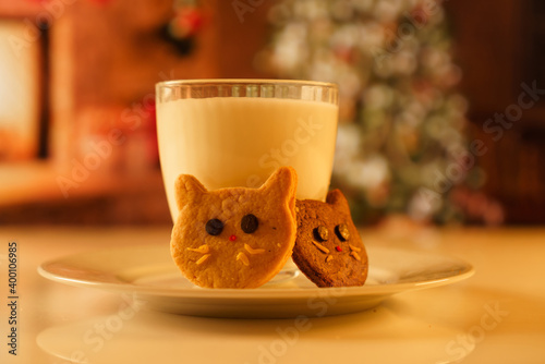 Fototapeta Cocoa and gingerbread cookies for New Year's Eve and Christmas themed. An image of a cat-like cookie and a glass of milk with a Christmas tree and fireplace in the background. obraz