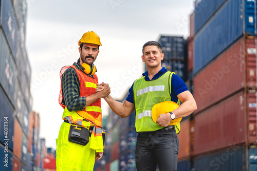Obraz na plátně Professional of two engineer container cargo foreman partners in helmets working successful handshake together into container for loading