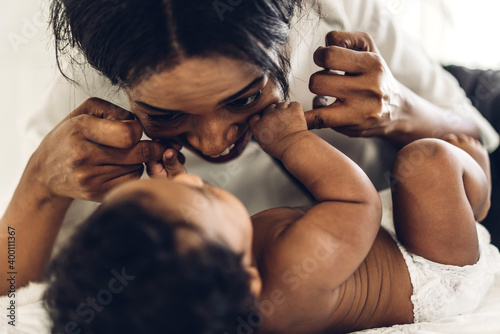 Fototapeta Portrait of enjoy happy love family african american mother playing with adorable little african american baby.Mom touching with cute son moments good time in a white bedroom.Love of black family  obraz