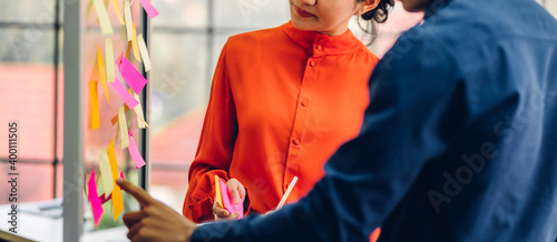 Fototapeta Casual creative happy two smile asian business people planning strategy analysis and brainstorm putting post it stickers note to share idea for startup project on glass board at modern office obraz