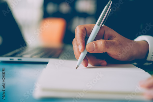 Fototapeta Woman hand writing down in small white memo notebook for take a note not to forget or to do list. obraz