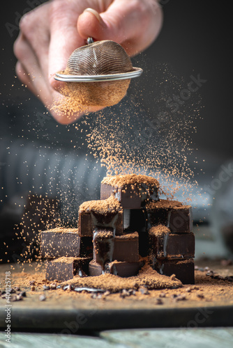 Fototapety, obrazy: Hand is sprinkling cocoa powder on delicious appetizing cubes of bitter dark chocolate
