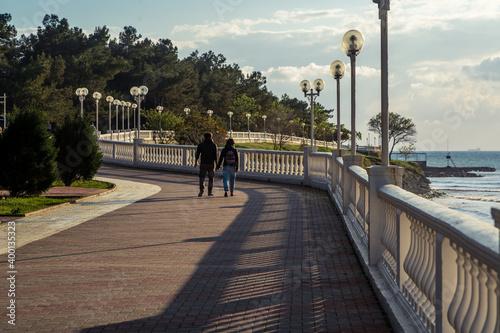 Fotografia A young couple walks along the Gelendzhik embankment at sunset