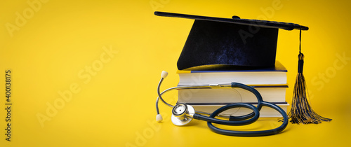 medical education - college graduation cap with stethoscope and books on yellow Fotobehang
