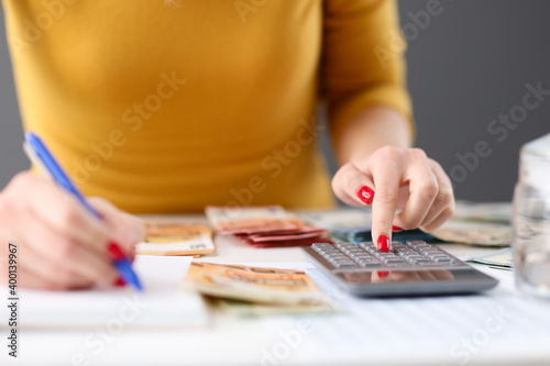 Fotografia, Obraz Woman is counting on calculator and writing with pen in notebook closeup