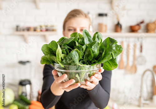 Young blond smiling woman holding a bowl of fresh spinach in the kitchen