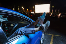 Close Up Of Woman Hanging Her Legs Out Of Car Window While Watching A Movie At Drive In Cinema From The Front Seat Of The Car