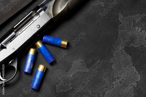 Fotomural Close up of hunting shotgun and cartridges on dark grey background