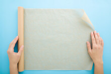 Young Adult Woman Hands Using Roll Of Baking Paper On Light Blue Table Background. Pastel Color. Closeup. Point Of View Shot. Top Down View.