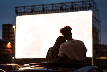 Silhouetted View Of Attractive Young Couple, Boy And Girl Embracing, Spending Time Together, Sitting In The Car While Watching A Movie In A Drive In Cinema