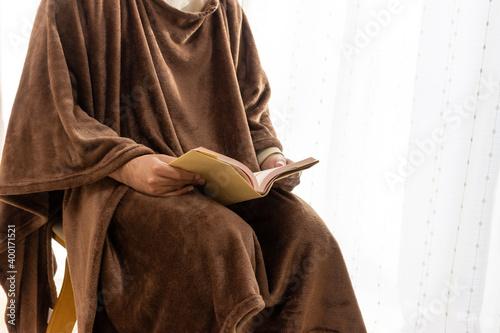 温かい恰好で読書をする男性 Fotobehang