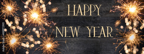 Fototapeta HAPPY NEW YEAR 2021 background greeting card - Firework, sparklers and bokeh lights on rustic black wooden wood wall texture obraz