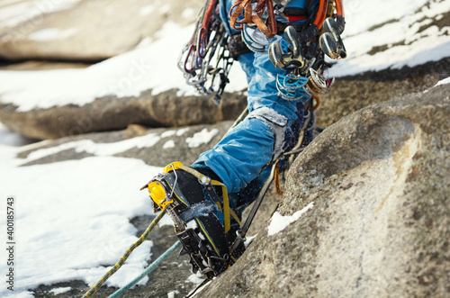 Foto Crampons on high-altitude boots of a mountaineer during a winter ascent in cold conditions in the mountains, close-up