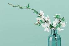 Spring Or Summer Festive Blooming With White Flowers Fruit Tree Branches In Small Green Glass Vase Against Tender Green Background. Fresh Floral Background With Copy Space