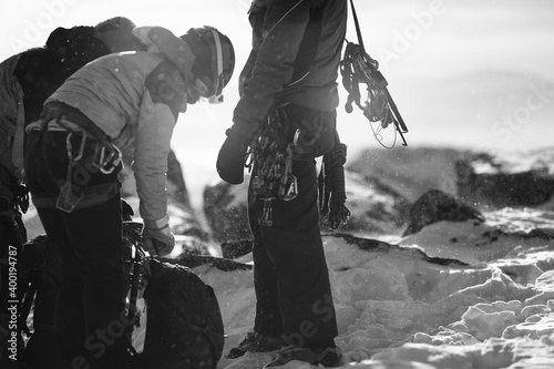 Canvastavla Silhouettes of climbers on a background of snow-covered rocky relief in the winter mountains, details of equipment and outfits, close-up, black and white