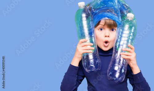 Girl hold trash bag and plastic bottle and shows interest in environmental issues isolated on blue background Wallpaper Mural