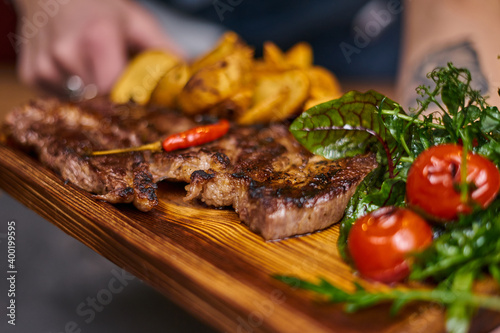 Fototapeta Beef steak with hot chili pepper on a wooden board obraz