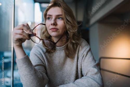 Fototapeta Focused young woman putting on glasses
