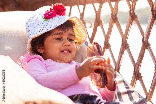 Canvastavla Playful Pretty Indian girl child, infant playing on a boathouse with rustic wooden furniture and giving adorable expressions