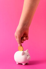 Hand Of A Child Putting A Coin Into Piggy Bank. Child Savings Concept. Banking For Children. Pink Rose Abstract Background.