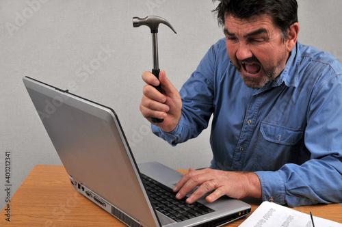 Obraz na plátně Homme énervé tapant avec un marteau sur son ordinateur portable