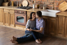 Tender Loving Young Male Husband Sit Barefoot On Cozy Wooden Warm Kitchen Floor Embrace Cheering Female Wife Hold Her On Knees Look In Eyes. Happy Lovers Enjoying Date At Home Spending Time Together