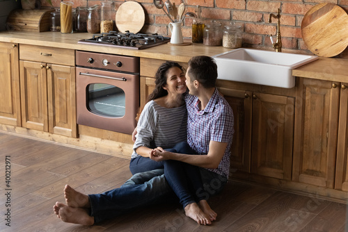 Obraz Tender loving young male husband sit barefoot on cozy wooden warm kitchen floor embrace cheering female wife hold her on knees look in eyes. Happy lovers enjoying date at home spending time together - fototapety do salonu