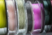 Many Reels With Fishing Line And Braided Fishing Line In Different Colors And Sizes