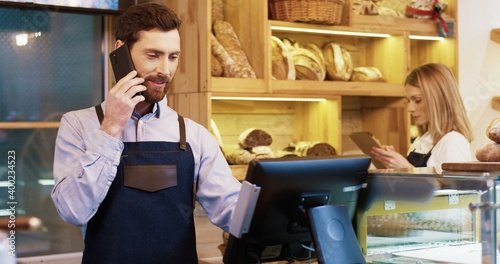 Canvastavla Portrait of Caucasian bearded handsome happy male baker standing in bakery at counter and speaking on cellphone
