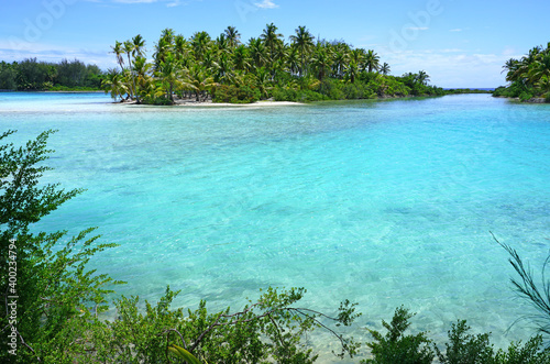View of a tropical landscape with palm trees, white sand and the turquoise lagoo Wallpaper Mural