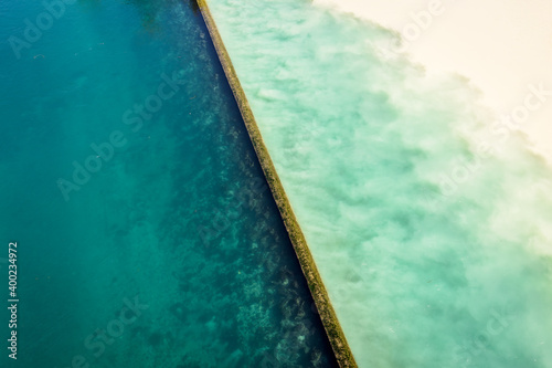 Obraz na plátně High angle view of the emerald blue waters of the Rhone river and the yellowish silty waters of the Arve river blending at their confluence called the Junction in Geneva, Switzerland